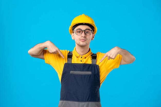 Вид спереди мужчины-строителя в униформе и шлеме на синей стене