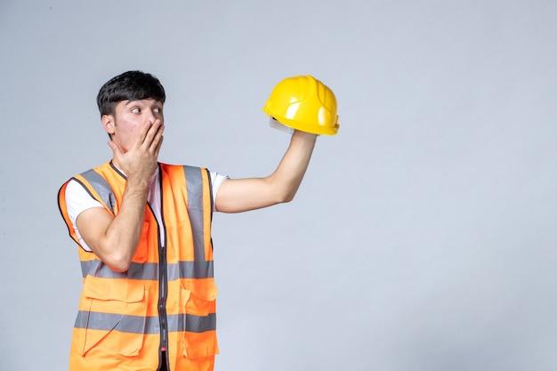 Вид спереди мужчины-строителя в форме, держащего желтый шлем на белой стене
