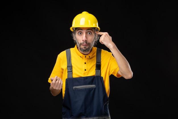 검은 벽에 제복을 입은 남성 건축업자의 전면 모습