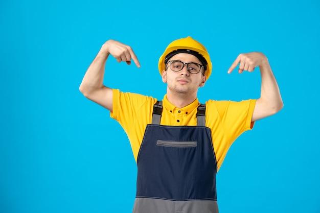 Вид спереди мужчины-строителя в униформе на синей стене