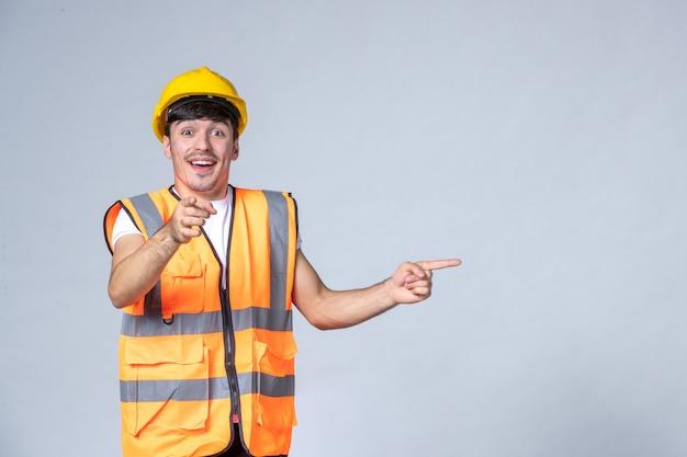 Вид спереди мужчины-строителя в униформе на белой стене