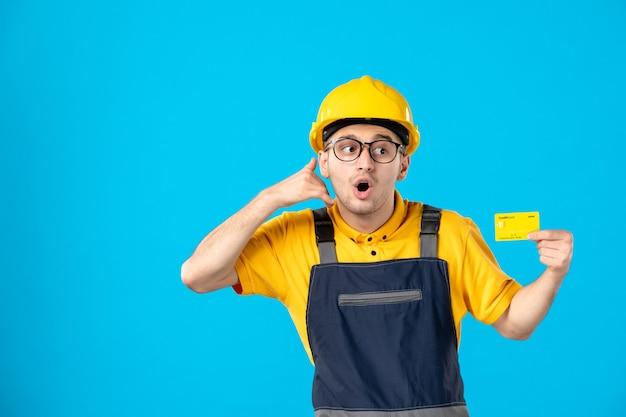 Вид спереди мужчины-строителя в форме с кредитной картой на синей стене