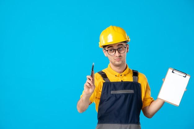 青い壁に彼の手でファイルノートと制服を着た男性ビルダーの正面図