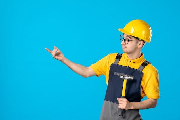 青い表面に彼の手でハンマーで制服を着た男性ビルダーの正面図