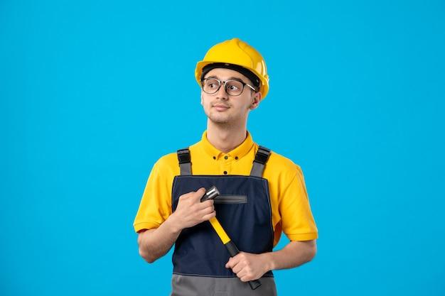 青い壁に彼の手でハンマーと制服を着た男性ビルダーの正面図
