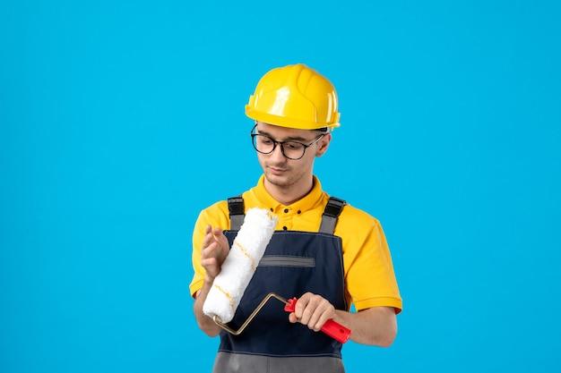 Вид спереди мужчины-строителя в униформе с малярным валиком в руках на синей стене
