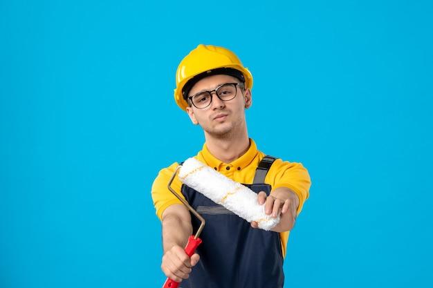 Вид спереди мужчины-строителя в униформе с малярным валиком на синей стене
