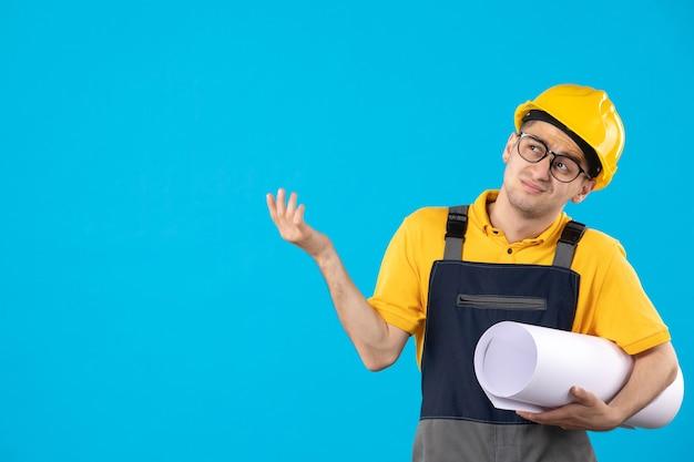 青い壁に紙の計画と制服を着た男性ビルダーの正面図