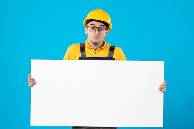 Вид спереди мужчины-строителя в форме с бумажным планом на синей стене