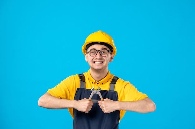 青い表面にペンチを手に持った制服を着た男性ビルダーの正面図