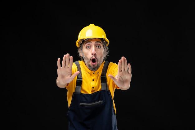 검은 벽에 노란색 유니폼을 입은 남성 건축업자의 전면 모습