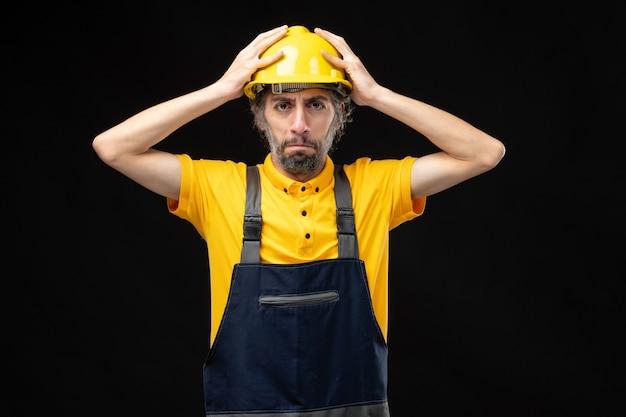 黒い壁に黄色い制服を着た男性ビルダーの正面図