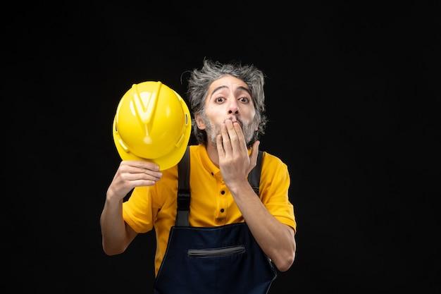 검은 벽에 노란색 유니폼을 입은 남성 건축업자의 전면 모습 무료 사진