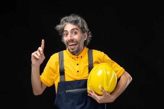 Вид спереди мужчины-строителя в желтой форме на черной стене