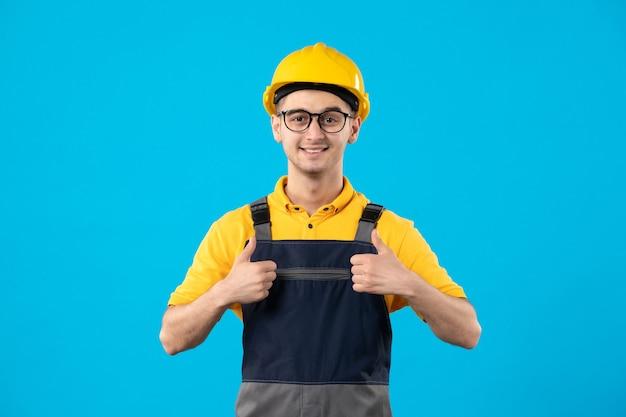 青い壁に黄色の制服を着た男性ビルダーの正面図