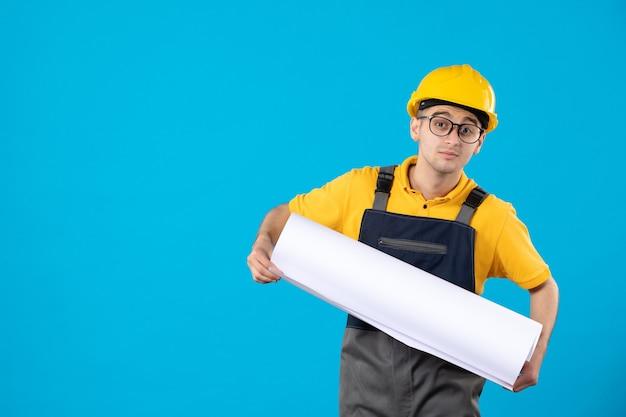 Вид спереди мужчины-строителя в желтой форме с планом чтения на синем