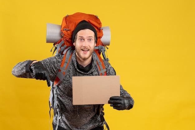 Вид спереди мужского туриста с кожаными перчатками и рюкзаком, держащим чистый картон