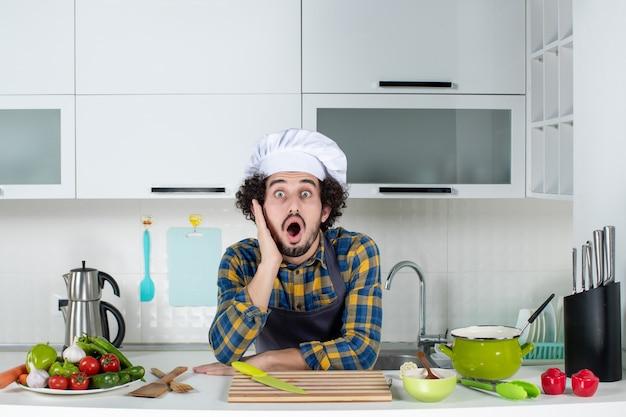 白いキッチンでショックを受けた新鮮な野菜を調理する男性シェフの正面図