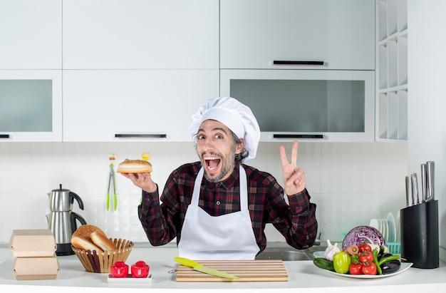 キッチンで勝利のサインを作るパンを保持している男性シェフの正面図