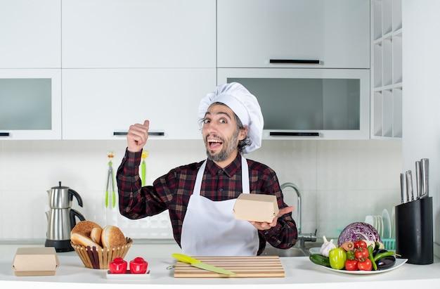 부엌에서 식탁 뒤에 서 있는 뒤를 가리키는 남성 요리사의 전면