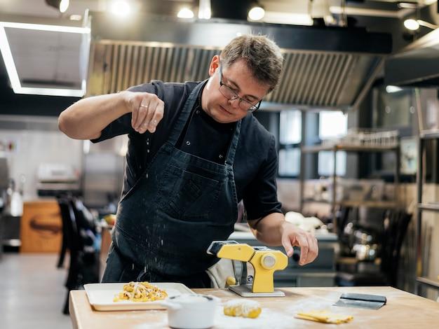 Вид спереди мужского шеф-повара, приправляющего тесто для пасты