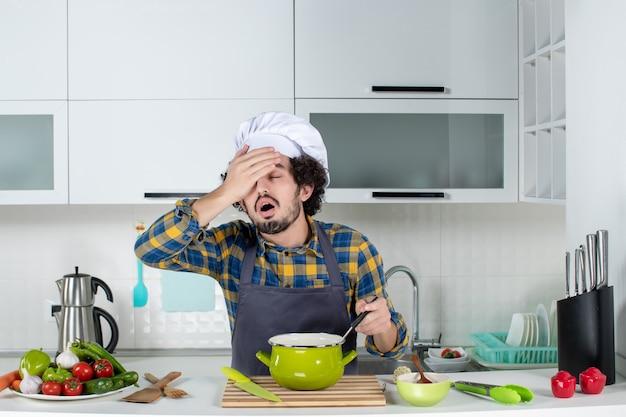 Вид спереди мужского шеф-повара со свежими овощами и держащего ложку в еде, чувствуя себя измученным на белой кухне