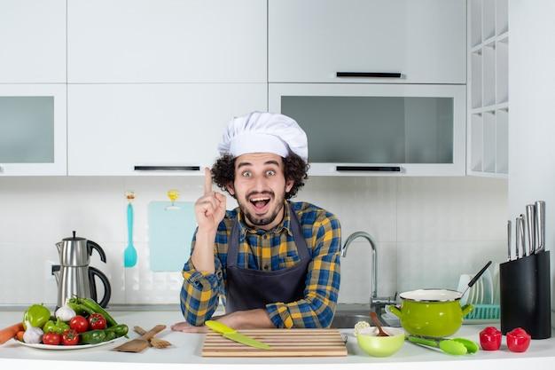 흰색 부엌에서 행복한 표정으로 가리키는 신선한 야채와 함께 남성 요리사의 전면보기