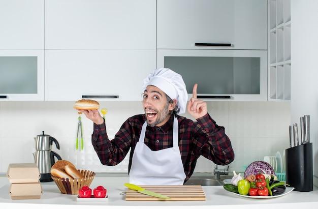 キッチンでアイデアを持って驚くべきパンを持っている男性料理人の正面図