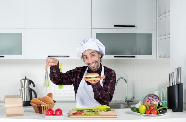 台所のテーブルの後ろに立っているテーブルの上のパンを指してハンバーガーを持ち上げている男性料理人の正面図