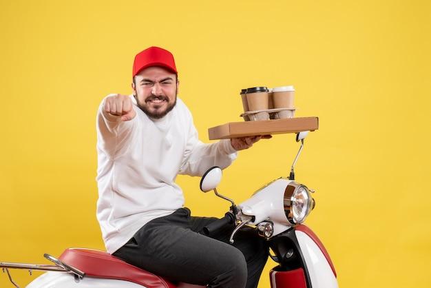 黄色の壁に配達コーヒーと食品を保持している男性の宅配便の正面図