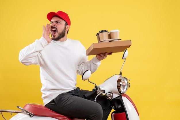 Вид спереди курьера-мужчины, держащего доставку кофе и еды на желтой стене