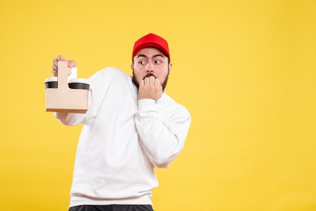 黄色の壁に配達コーヒーを保持している男性の宅配便の正面図
