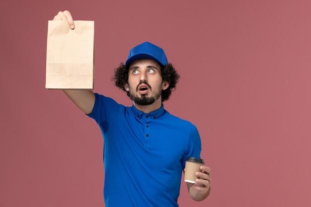 ピンクの壁に彼の手に配達コーヒーカップと食品パッケージと青い制服とキャップの男性の宅配便の正面図