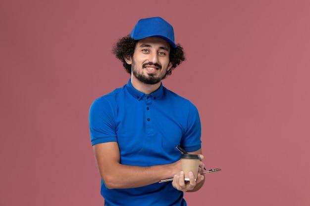 ピンクの壁にメモを書いている彼の手に配達コーヒーカップとメモ帳が付いている青い制服とキャップの男性宅配便の正面図