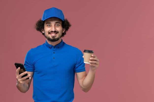 Вид спереди курьера-мужчины в синей форме и кепке с доставкой кофейной чашки и смартфона на руках на розовой стене