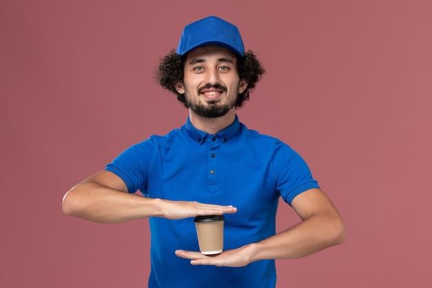 Вид спереди курьера-мужчины в синей форме и кепке с доставкой кофейной чашки на руках на розовой стене