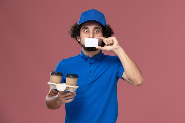 Вид спереди курьера-мужчины в синей форме и кепке с доставкой кофейных чашек и открыткой на руках на розовой стене
