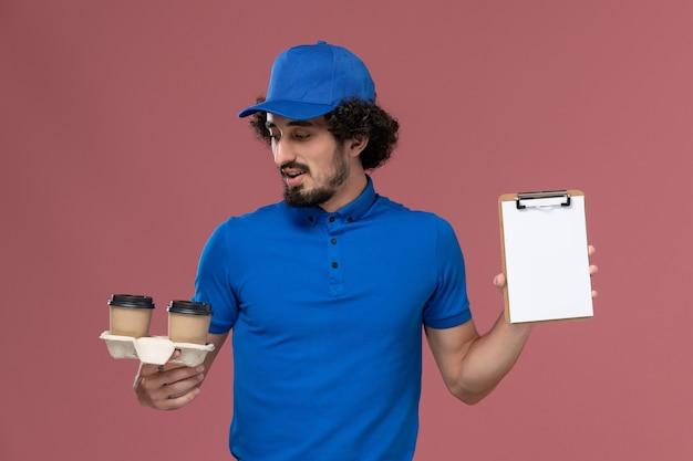 青いユニフォームとピンクの壁に彼の手に配達コーヒーカップとメモ帳とキャップの男性宅配便の正面図