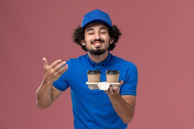 青い制服と帽子の男性の宅配便の正面図ピンクの壁に臭いが彼の手に配達コーヒーカップ