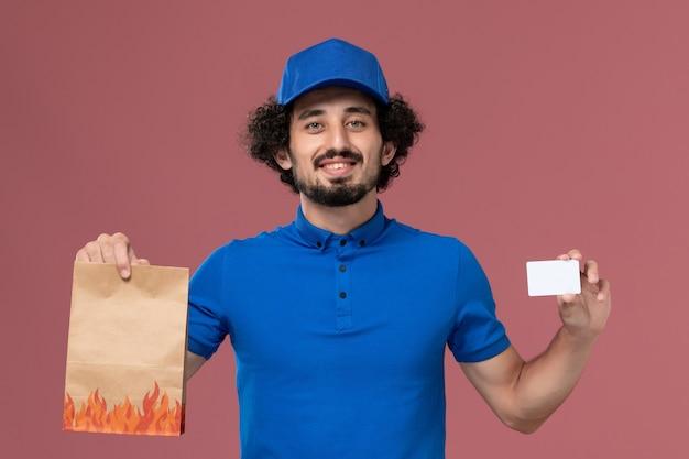 ピンクの壁に彼の手にカードと配達食品パッケージと青い制服キャップの男性宅配便の正面図