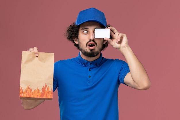 Вид спереди курьера-мужчины в синей форменной кепке с карточкой и пакетом продуктов для доставки на руках на розовой стене
