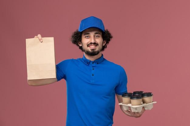 ピンクの壁に彼の手に配達コーヒーカップと食品パッケージと青い制服キャップの男性宅配便の正面図