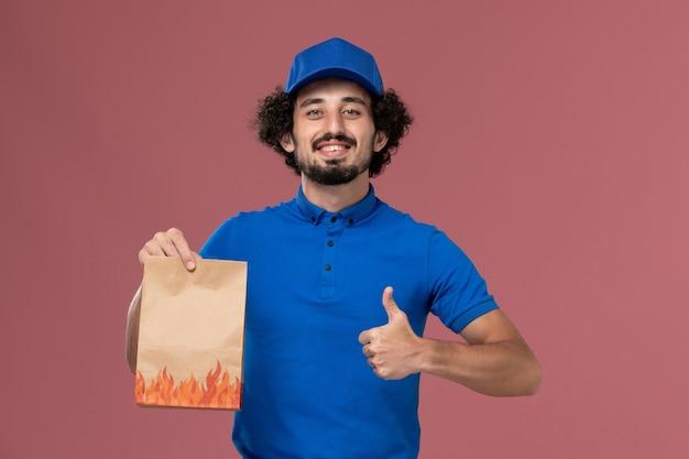 Вид спереди курьера-мужчины в синей форменной кепке с бумажным пакетом еды на руках на светло-розовой стене