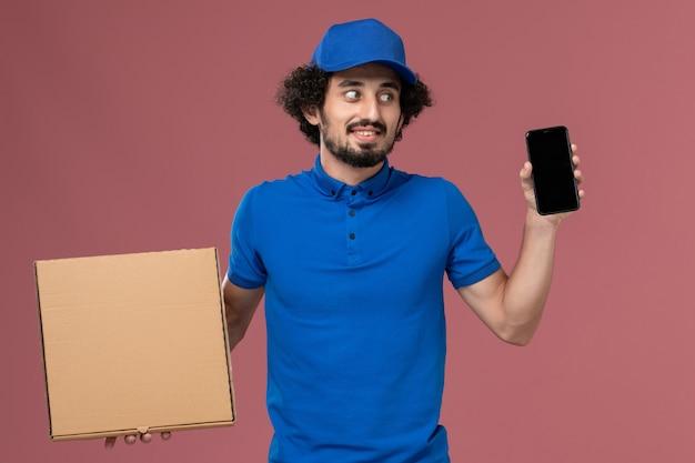 淡いピンクの壁にフードボックスと彼の手に電話と青い制服キャップの男性宅配便の正面図