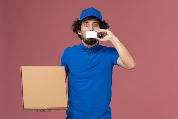 Вид спереди курьера-мужчины в синей униформе с коробкой для еды и белой пластиковой картой на руках на розовой стене