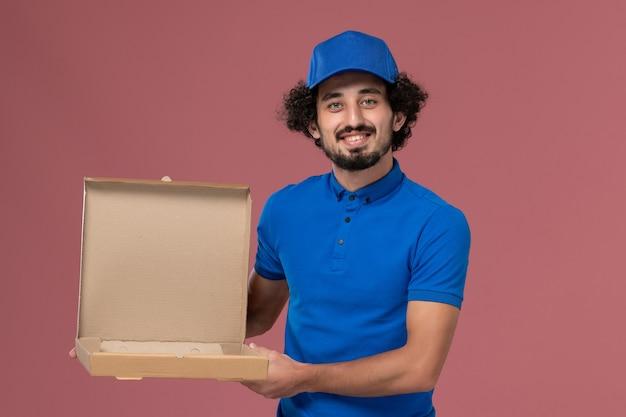 淡いピンクの壁に彼の手にフードボックスと青い制服キャップの男性宅配便の正面図
