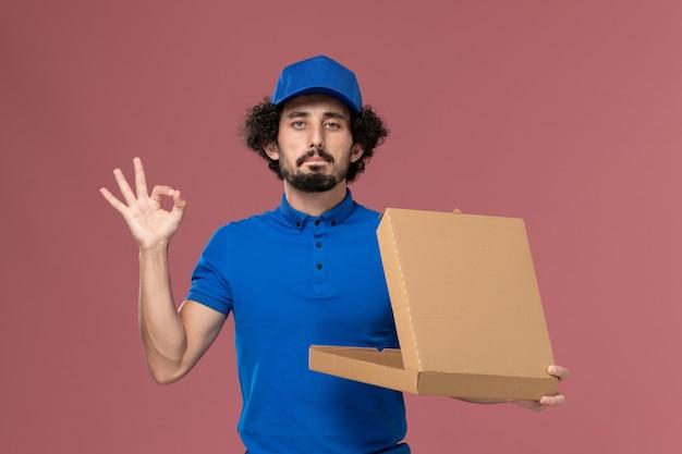淡いピンクの壁にそれを開く彼の手にフードボックスと青い制服キャップの男性宅配便の正面図