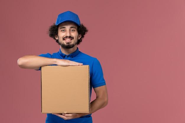 Вид спереди курьера-мужчины в синей униформе с коробкой для еды на руках, улыбаясь на светло-розовой стене