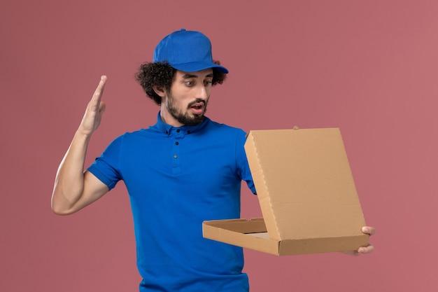 淡いピンクの壁に彼の手に開いたフードボックスと青い制服キャップの男性宅配便の正面図