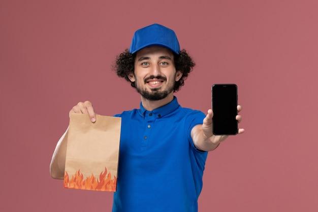 Вид спереди курьера-мужчины в синей форменной кепке со смартфоном и пакетом продуктов для доставки на руках на розовой стене